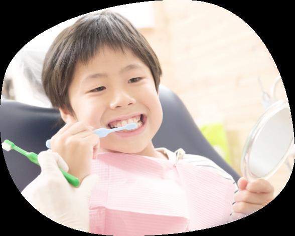 小児が正しい歯磨きを教えてもらってるイメージ